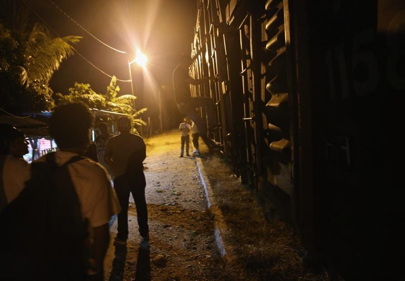 Migrant people boarding freight train