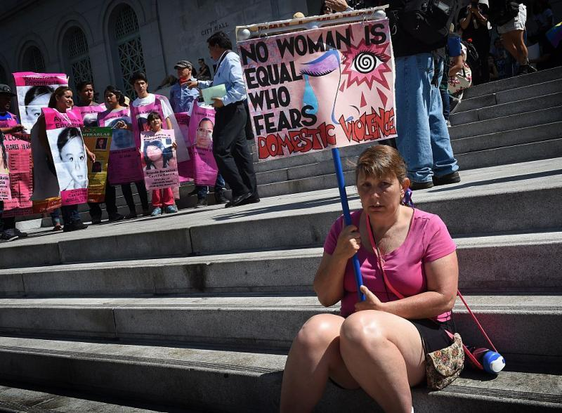 A woman protests against domestic violence as she joins other women's rights advocates in an International Women's Day march in downtown Los Angeles, California on March 8, 2015. AFP PHOTO/ MARK RALSTON (Photo credit should read MARK RALSTON/AFP via Getty Images)
