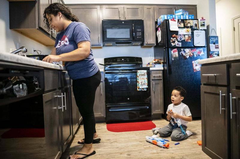 Destiny Clark, left, 22, prepares to cook breakfast for her son Tevin Webster, 4, Friday, Jan. 25, 2019, at the newly built Family Scholar House campus in Louisville, Ky.