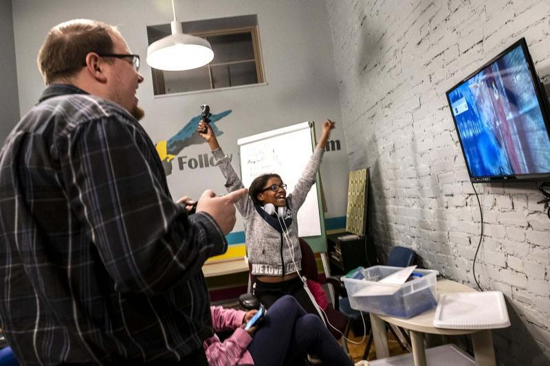 Danielle Washington, right, attends Volunteers of America's Teens with a Purpose program, which gives teen living in the transitional housing and emergency family shelter, a space to interact with each other and volunteers including Greg Hummel, left.