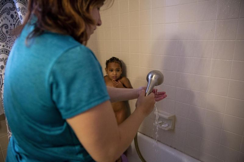 Tiana cowers from her mother in the corner of the shower because she does not like having her hair washed. Even though Angelica is ill from intensively cleaning her home the day prior, she bathes her two girls and applies prescription ointments to their skin. [Photo by Angela Piazza]