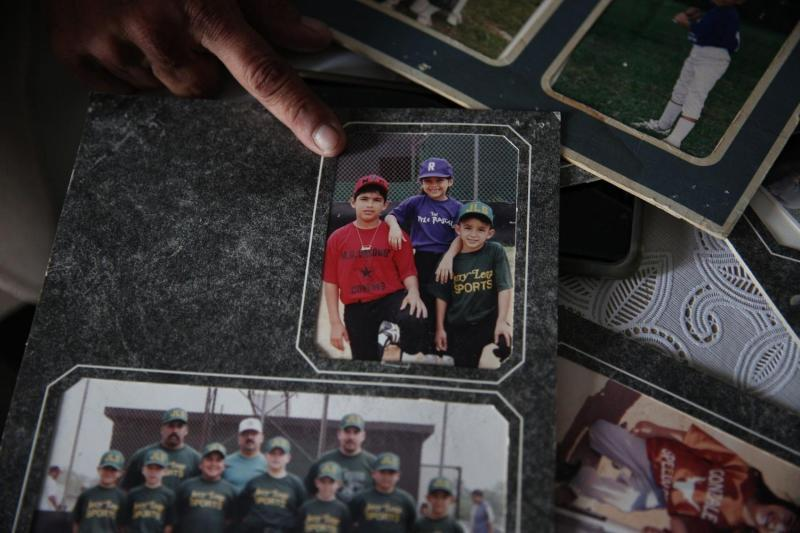 Theresa Martinez, 50, shows old photographs of her kids in Little League. Martinez was involved with the youth sports program in Bloomington for about three decades and is struggling to get youth sports started again.