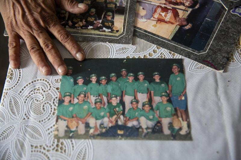 Theresa Martinez shows old photographs of her kids in Little League in Bloomington.