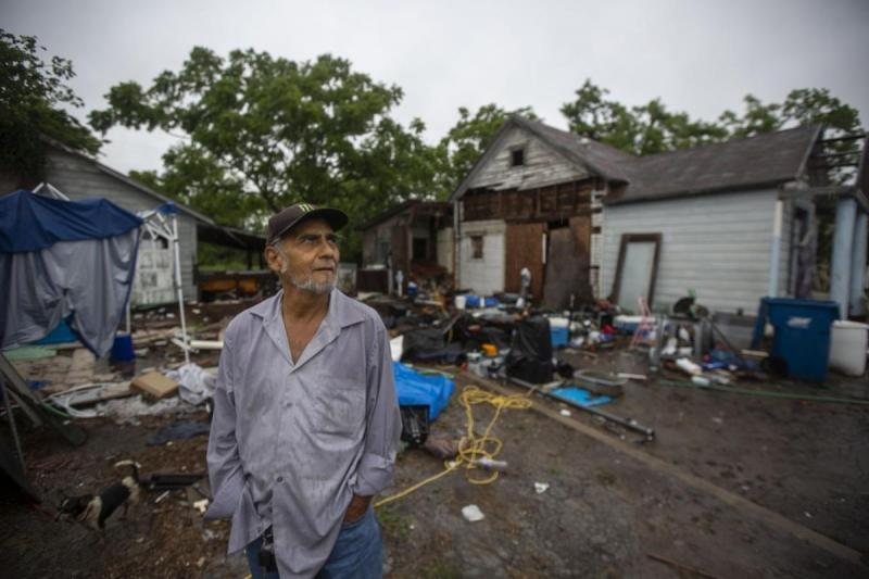 U.S. Army veteran Reynaldo Garza, 70, stands in front of his house at 305 Locke St. in Woodsboro. The home was destroyed in Hurricane Harvey, forcing Garza to live in his vehicle.