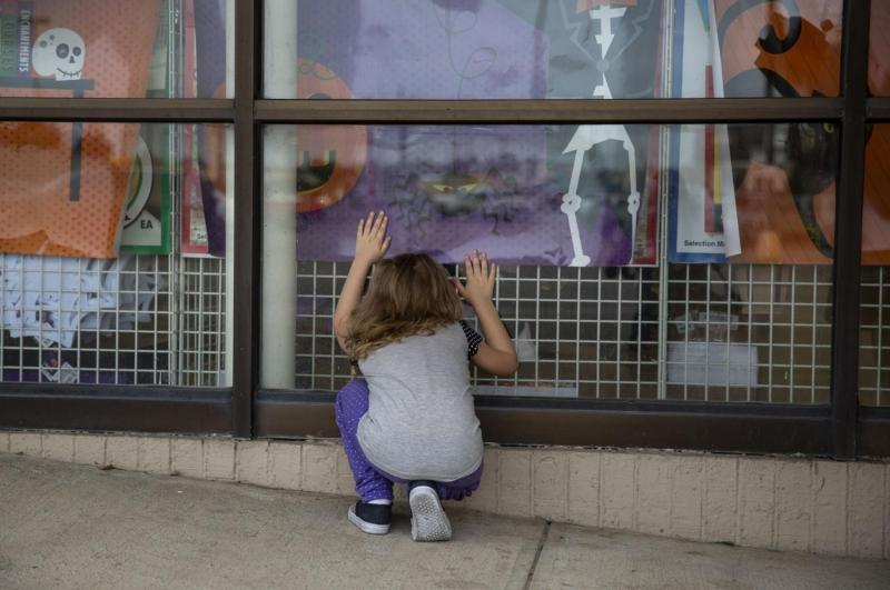 Zoey looks at Halloween decorations through the window of Dollar Tree while her mother and sister attempt to collect enough donation money to rent a motel room for the night.