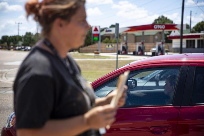 """A driver stopped at a red light ignores Devan Orsak, 37, who holds a sign that says """"Need Gas."""" Orsak said drivers often ignore, stop far away, roll up windows and, on one occasion, throw food at her. Even though she and her seven children are no longer homeless, Orsak says she must continue to panhandle to pay for food, gas and other basic needs for her family until she finds a steady job."""