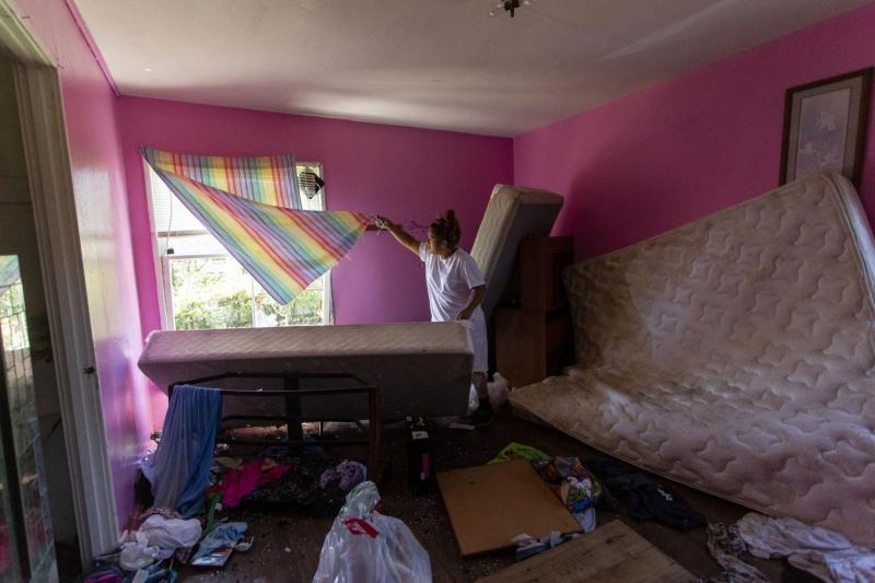 Barrientes lifts a curtain to show a broken window. The mother said she attempted to barricade the window with a mattress during Hurricane Harvey, but the winds were too strong. Broken glass, clothing and a water-damaged mattress are scattered across the bedroom floor.
