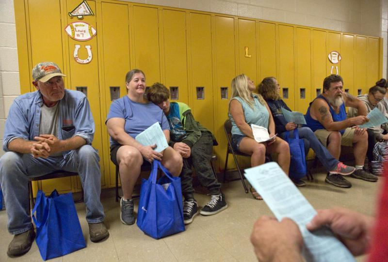 Folding chairs line a hallway at Lee County High School during a RAM Clinic in September, filled with people waiting for vision care. Michael Mannon, 50, of Jonesville and Michelle Ely, 48, and her 12-year-old son, Michael Ely, who live in Dryden, move along the chairs as they wait to enter a classroom and have their vision checked.