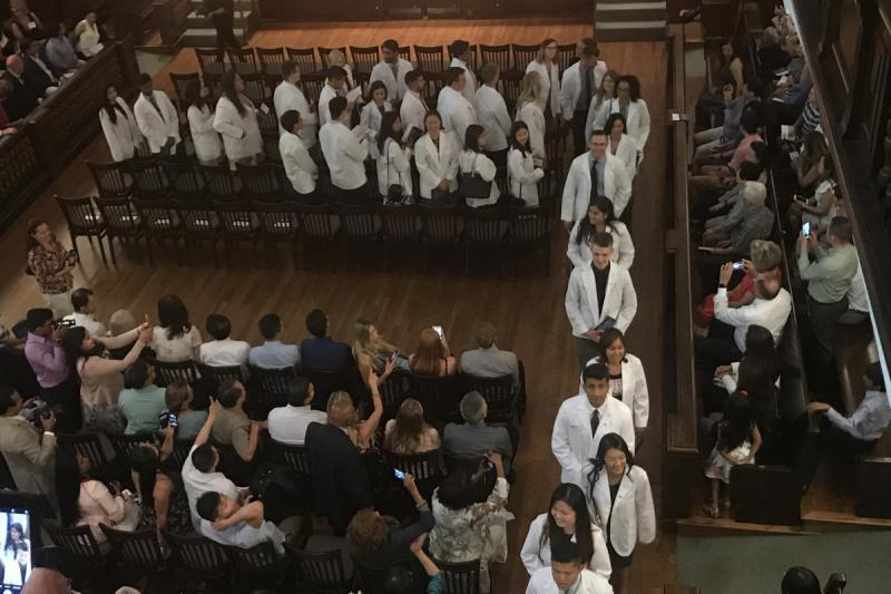 The inaugural class of the California University of Science and Medicine exits in procession after donning their white coats.