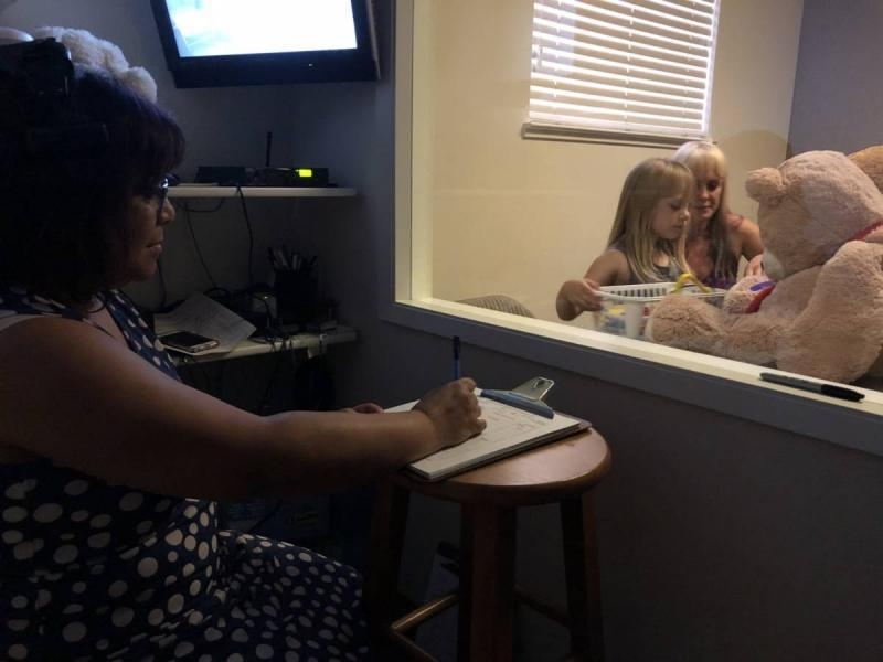 Therapist Laurie Taylor observes mother and daughter from behind the two-way mirror. (Laura Klivans/KQED)