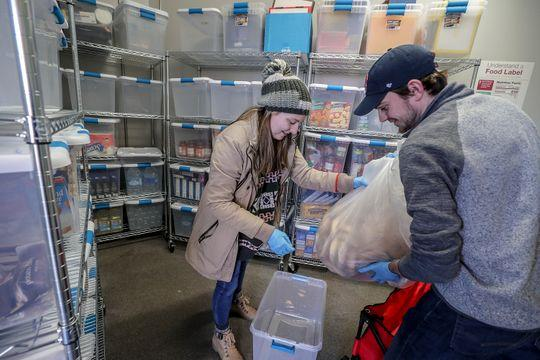 Henny Ransdell, left, and Ryan Buckman, right, take a bag of bagels donated by Einstein Bros. bagels, and put them into a plastic bin at U of L's food bank. Jan. 28, 2019 (Photo: Michael Clevenger/Courier Journal)