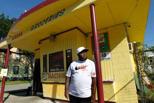 """June Thomas, 48, stands in front Aaran Groceries, where he is a partner in the business. Thomas is no stranger to violence. """"I've seen a lot of bodies and a lot of people hurt. That stuff stays on your mind,"""" he said. (Photo: Angela Peterson/Milwaukee Journal Sentinel)"""