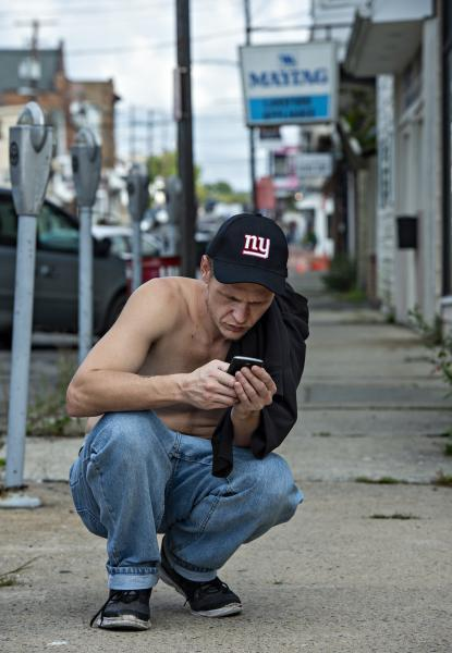 Travis Litts crouches down on the sidewalk along East Ridge Street in Lansford to answer text messages. Rick Kintzel / The Morning Call