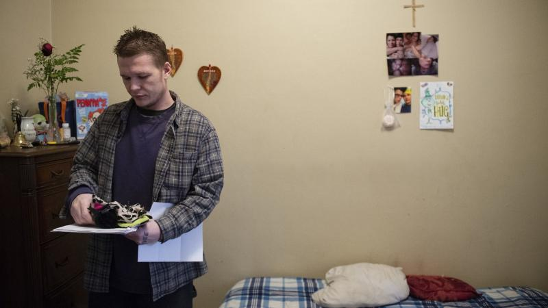 Travis Litts stands in his bedroom at his Lansford apartment while holding clothing and medical paperwork. Rick Kintzel / The Morning Call