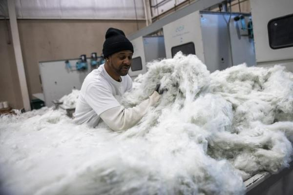 Melvin Peterson of Homestead separates recycled polyester used for pillows. (Michael M. Santiago/Post-Gazette)