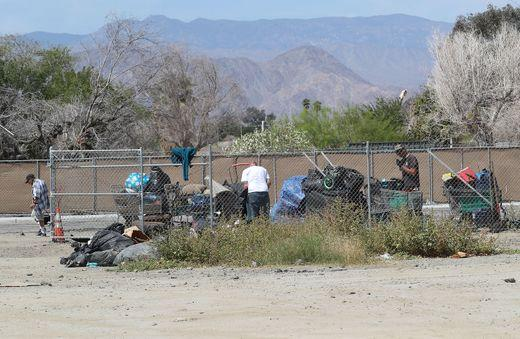 People experiencing homelessness prepare to move their camps and belongings off of a large vacant lot. (Jay Calderon/The Desert Sun)