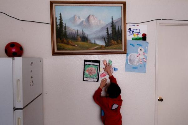 """Kender Ricardez Tobon, 5, stamps a drawing he made at school on the walls of his home. He lives in a small apartment complex on the East Side of Salinas with his grandmother Eufemia """"Jenni"""" Aguilar. SEBASTIÁN HIDALGO FOR THE SALINAS CALIFORNIAN AND CATCHLIGHT.IO"""