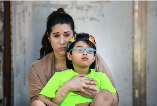JESSICA GRIFFIN / STAFF Cristine Pagan, with her son Dean, who was poisoned by flaking lead paint at Comly Elementary School.
