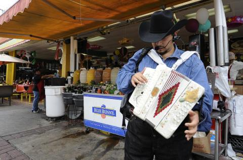 A strolling musician performs at one of Los Angeles' largest swap meets.