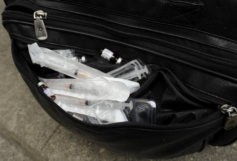 Daniel Hancz, Pharmacist and Investigator for the Los Angeles County Department of Public Health shows illegal prescription drugs and hypodermic needles confiscated from an unlicensed physician's medical bag.