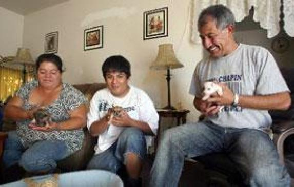 Calixto Orantes, right, his son Julio, 17, center, and wife Edel, left, play with their new puppies at their home.