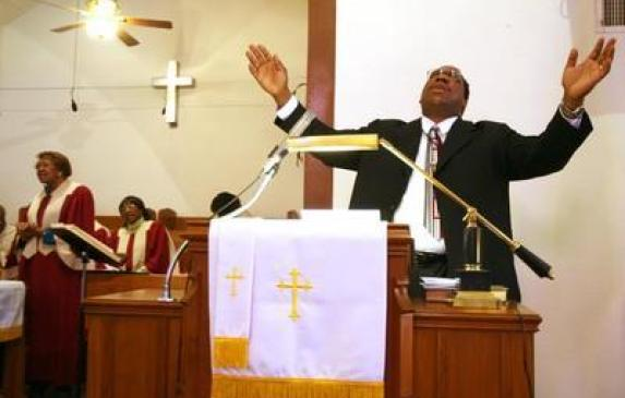 The Rev. Jeffrey M. Parker prays during a service at Community Reformed Church in the Sobrante Park neighborhood.