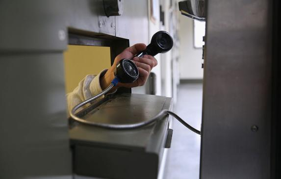 An immigrant makes a call from a cell at the Adelanto Detention Facility in Adelanto, California.