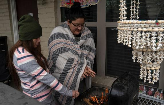Karla Perez and Esperanza Gonzalez warm up by a barbecue grill during power outage caused by the February winter storm.