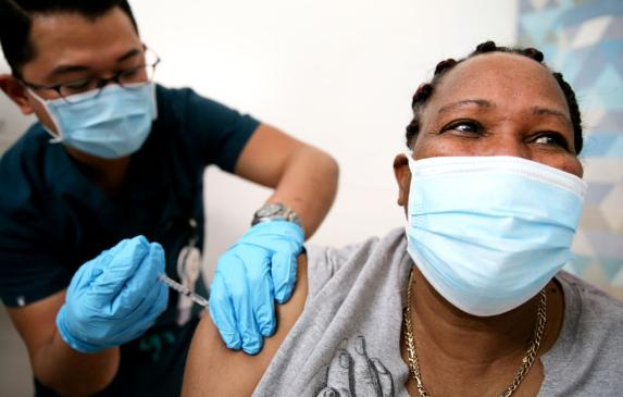 Lorraine Harvey, an in-home care worker, receives her first dose of the COVID-19 vaccine