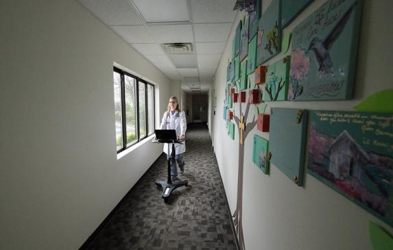 Physician walks down hallway