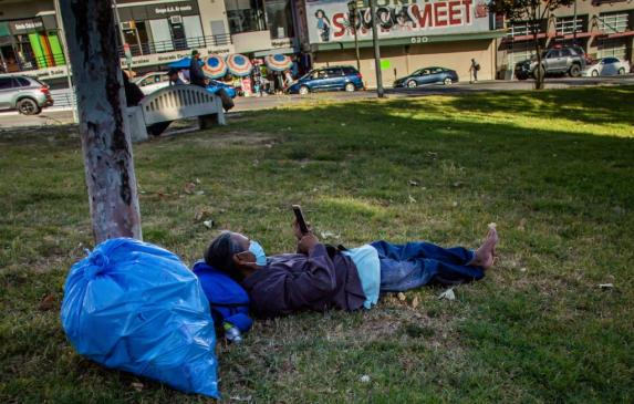 A homeless man lies on the grass in MacArthur Park in Los Angeles in May.