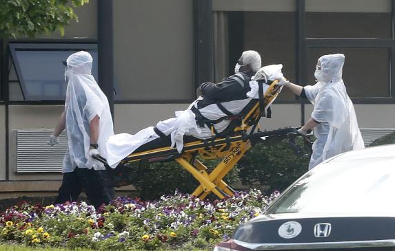 A nursing home resident is wheeled on a stretcher from an ambulance into the Canterbury Rehabilitation and Healthcare Center