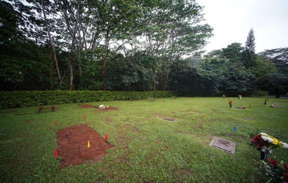 Fresh earth covers the grave of Neita Bolkeim at Hawaiian Memorial Park in Kaneohe.
