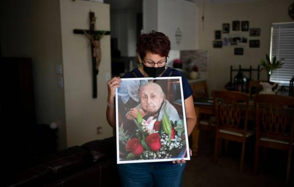 Marisela Munoz holds a photo of her aunt, Evangelina C. Martinez, who raised her since birth, at her home in Canyon Country, Fri