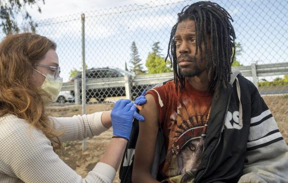 The Community Lead Advocacy Program (CLAP) brought vaccines to a homeless encampment in the Valley Hi area. Javon Coleman was am