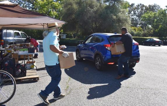 Volunteers help load boxes of food into vehicles after asking drivers how many boxes of food they want on June 4, 2021