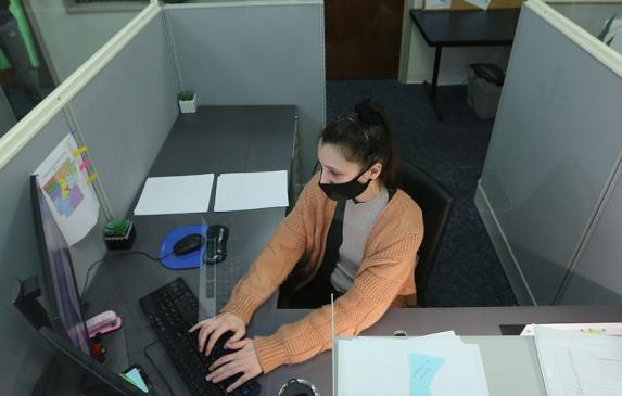 Brittany Irby, a state child abuse hotline operator, works on abuse reports at her workstation