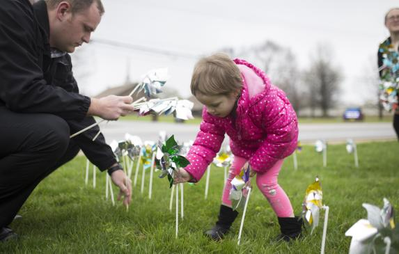 Elizabeth Crouch, 4, (center) places pinwheels in the ground with Det. Adam Corbett