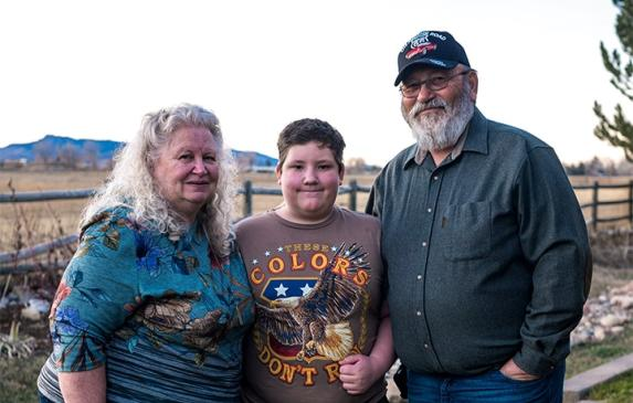 Child standing between Grandparents
