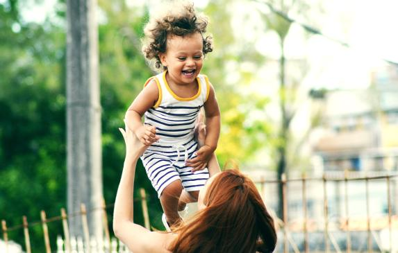 woman holding toddler girl up in the air