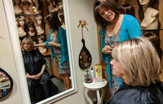 Lemonade Locks wig boutique owner Kelly Giblin fits a hairpiece onto retired Kern County Deputy Sheriff Brenda Blanton, who suff