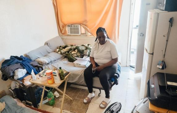 Kim Moore sits on her bed in a small unit of an unpermitted Mid-City apartment complex cited by the city in 2019.