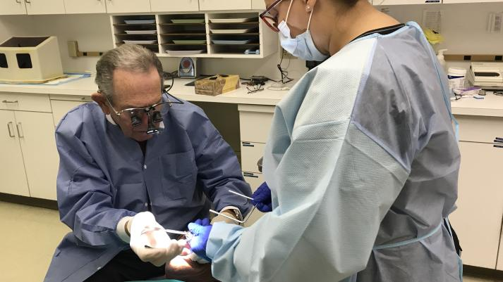 Daryl Ruby, left, Juan Sevilla, center, and Bertha Gonzalez, right. Ruby and Gonzalez work to extract a decayed tooth on Sevilla